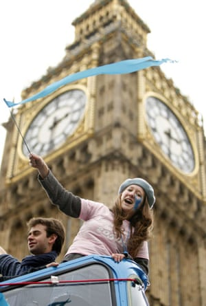 Wave climate change demo: A demonstrator waves a blue flag near Big Ben during a climate change march