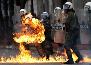 Athens demonstrations: A riot policeman's clothing catches fire after a petrol bomb was thrown