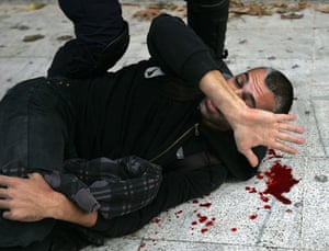 Athens demonstrations: An injured protestor is arrested by riot policemen during clashes