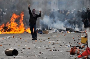 Athens demonstrations: A demonstrator shows a finger to riot police during a protest in Athens