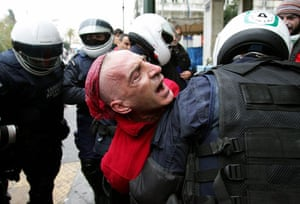 Athens demonstrations: Riot policemen detain a protester during clashes