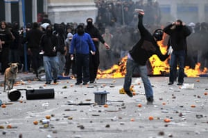 Athens demonstrations: A demonstrator throws a stone at riot police during a protest