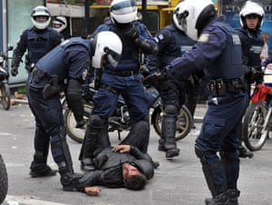 Athens demonstrations: Police detain an injured demonstrator during a massive demonstration