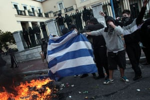 Athens demonstrations: Demonstrators burn a Greek flag during clashes in central Athens