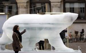 Copenhagen diary: A woman touches an ice sculpture of a polar bear in downtown COP15