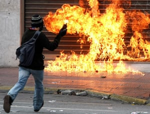 more voilence in athens : A protester prepares to throw a petrol bomb inAthens