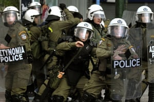 more voilence in athens : Riot police members protect themselves from stones