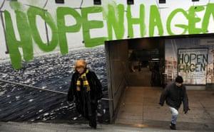 Copenhagen diary: Cop15 : Commuters walk beneath a logo of Hopenhagen