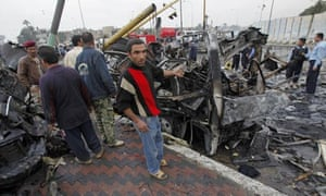 Iraqis gather at the site of a bomb attack near the Labour Ministry building in Baghdad, Iraq.