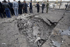 Baghdad bomb attacks: Iraqi security personnel gather near a crater caused by a bomb attack