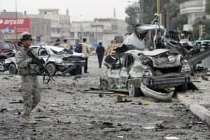 Baghdad bomb attacks: A US soldier stands guard near the wreckage of vehicles after a bomb attack