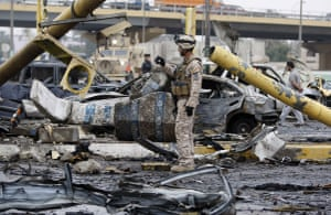 Baghdad bomb attacks: An Iraqi soldier takes pictures at the site of a bomb blast on Cairo Street