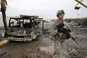 Baghdad bomb attacks: A US soldier walks past a burnt out bus at the site of a bomb attack