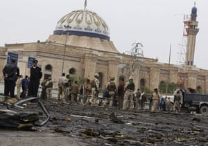 Baghdad bomb attacks: Soldiers and police secure the site of a bomb blast on Cairo Street