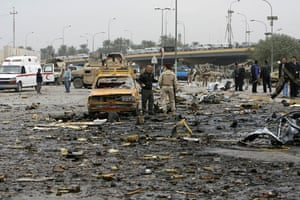 Baghdad bomb attacks: Iraqi security personnel are pictured at the site of a bomb attack