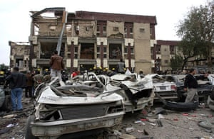 Baghdad bomb attacks: Iraqis gather near destroyed cars outside a criminal court building