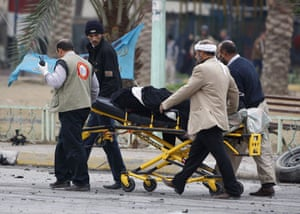 Baghdad bomb attacks: Iraqis evacuate a wounded man after a bomb blast on Cairo Street
