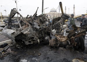 Baghdad bomb attacks: Policemen examine the wreck of burnt out vehicles at the site of an attack