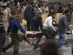 Baghdad bomb attacks: People evacuate the body of a victim killed by bomb attack
