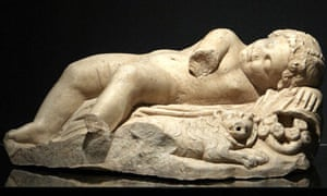 A marble statuette of a sleeping Eros and a lion next to him
