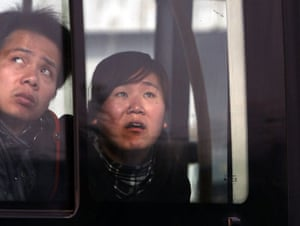 Beijing fire: People on a bus look at the fire damage as they pass the Mandarin Oriental