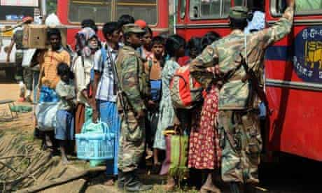 Ethnic Tamil civilians board a vehicle to go to a camp for internally displaced people in Vishvamadu