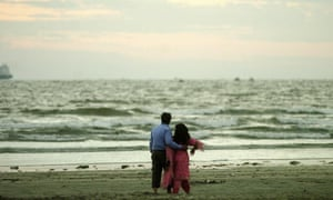 A Pakistani young couple walk on a beach on 2007's Valentine's Day in Karachi
