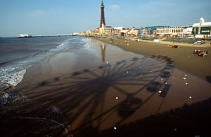 Big wheels : A ferris wheel on a pier casts a shadow on Blackpool Beach.