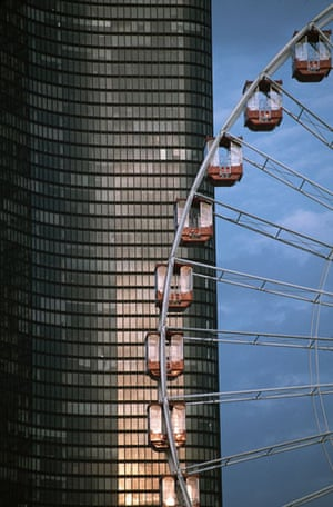 Big wheels : A close-up of a ferris wheel against a skyscraper in Chicago, Illinois.