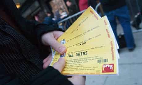 A ticket tout outside a London gigA ticket tout holds outside a London gig.