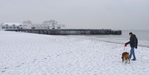 Gallery Snow in England: Southsea: A man walks his dog along the beach.