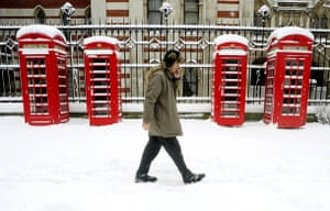 Gallery Snow in England: London: A man chats on his phone as he passes telephone boxes.