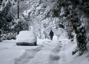 Gallery Snow in England: Carshalton:  A man walks in the tyre tracks left by cars.