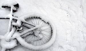 A fallen bicycle lies in the snow in Cambridge