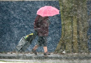 Gallery Snow update: Diss, Norfolk: An elderly shopper walks in a snow shower.