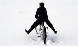 A boy cycles through the snow