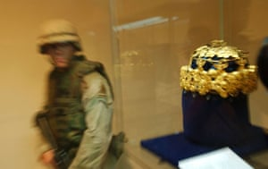 Baghdad museum : a soldier walks in front of a gold crown of Nimrud gold in Baghdad museum