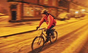 A cyclist braves the early morning roads in Bristol after heavy snow in south-west England
