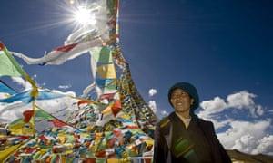 Woman stands beside Buddhist prayer flags in Tibet