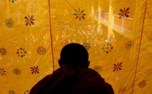 Kathmandu Uprising day: A monk looks through a curtain during Uprising day in Kathmandu, Nepal.