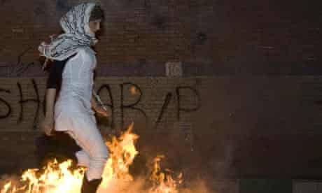 A woman jumps over a fire during the Chaharshanbeh Soori festival in Tehran