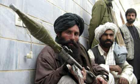 A former Taliban soldier crouches with his weapon