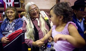 An elderly native American with his granddaughter