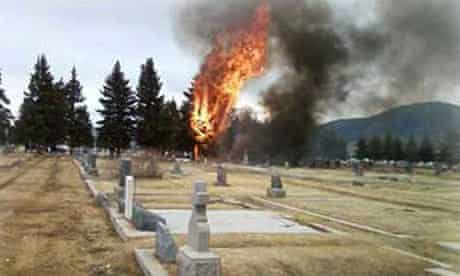Flames and billowing smoke rise after a private passenger plane crashed into a cemetery in Montana