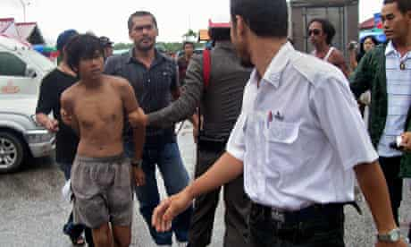 Thai police escort one of the suspects in the murder of Malcolm Robertson, on his yacht in Thailand.