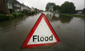 A flood sign warns of flooded areas following the torrential rain