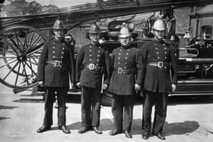 Firefighter uniforms: 1934: London firemen wearing the new and old versions of their headgear
