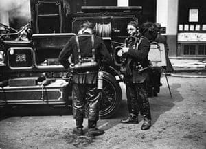 Firefighter uniforms: 1925: Firemen fixing on their smoke helmets