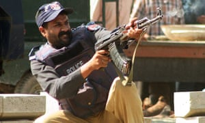 A policeman fires at gunmen at the police academy in Lahore