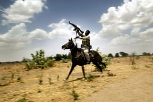 Darfur atrocities: A Sudanese Janjaweed fighter rides a horse in Sudan's west Darfur region